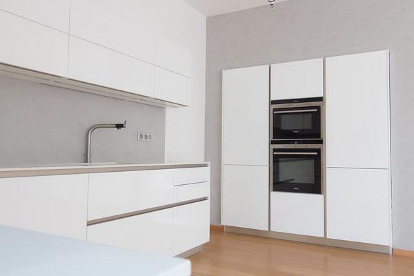Kuchyně bílá vysoký lesk betonová stěrka